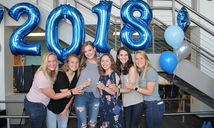 group of graduating women in front of 2018 balloons