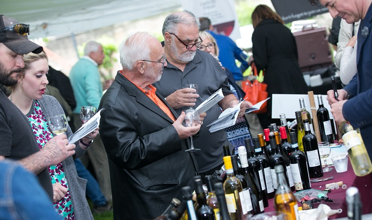 guests reviewing Wine Festival program by table of wine