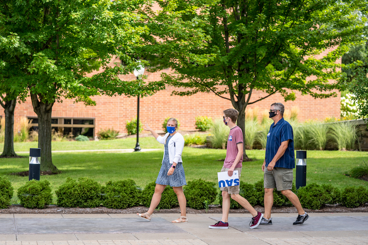 woman with a mask giving a guided tour of campus to a father and son wearing masks.